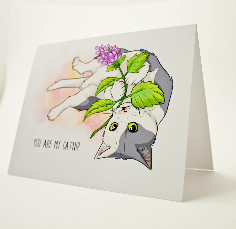 cat holding flower on card