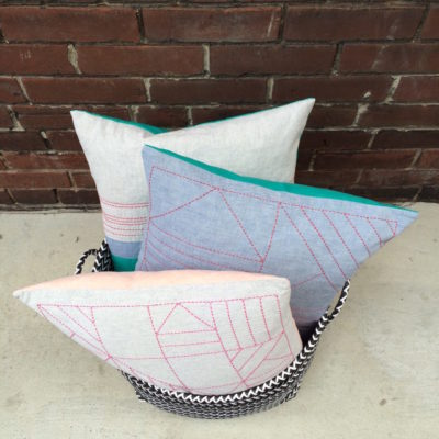 handmade pillows with geometric shapes in basket