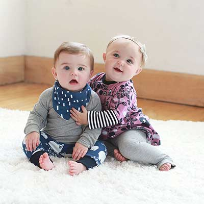 two babies smiling with handmade clothes